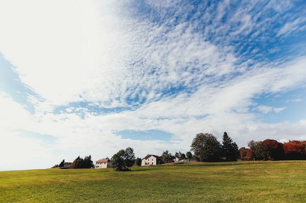 Paesaggio di campi verdi, case private in lontananza, belle nuvole nel cielo