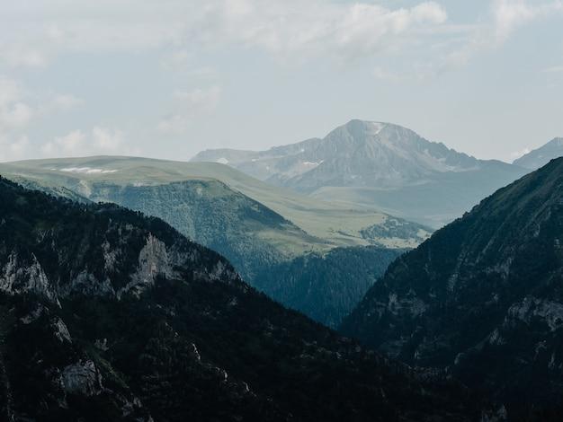 Paesaggio alte montagne nebbia nuvole natura aria fresca. foto di alta qualità