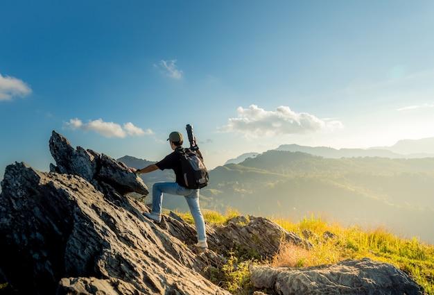 L'immagine del paesaggio dei fotografi maschii sta scalando alla cima di una montagna rocciosa.