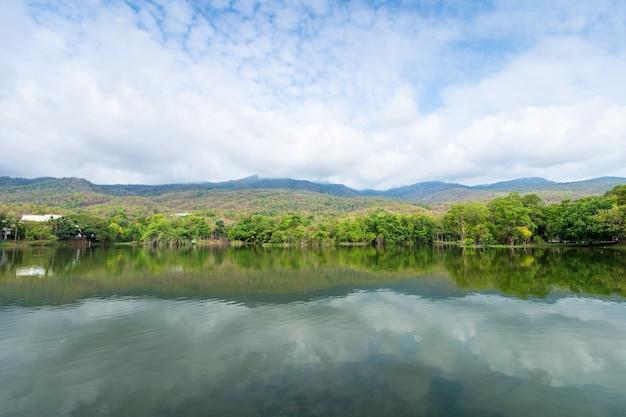 Vista sul lago del paesaggio all'università di ang kaew chiang mai nella foresta naturale vista sulle montagne primavera cielo blu sullo sfondo con nuvole bianche.