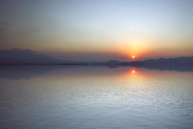 Il paesaggio di un lago con uno sfondo di cielo al tramonto