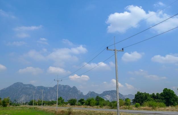 Paesaggio: montagne, cielo azzurro, nuvole, palo elettrico, piante verdi. agricola in thailandia.