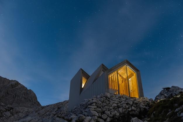 Paesaggio di montagne con una casa in cima