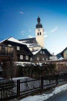Paesaggio di vecchia chiesa cattolica al villaggio austriaco coperto da snow