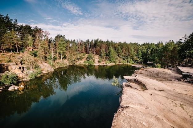 Il paesaggio di una vecchia cava di granito industriale allagata riempita d'acqua