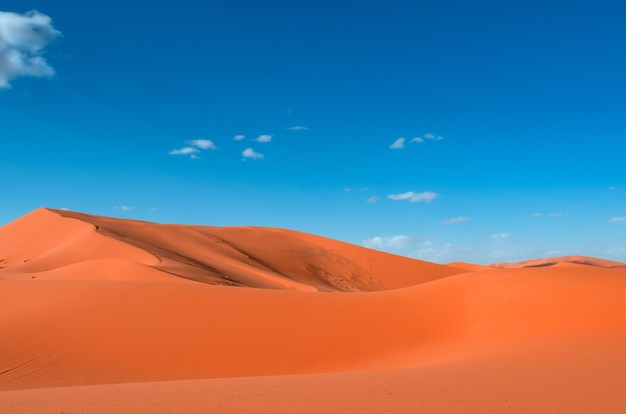 Paesaggio di dune di sabbia arancione contro un cielo blu