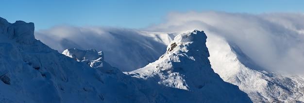 Panorama del paesaggio delle montagne invernali con rocce nella neve e nel gelo. catena montuosa tra le nuvole. carpazi ucraini