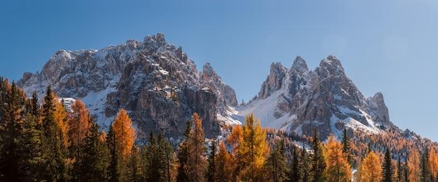 Panorama del paesaggio con montagne e alberi autunnali luminosi, cielo blu chiaro, dolomiti