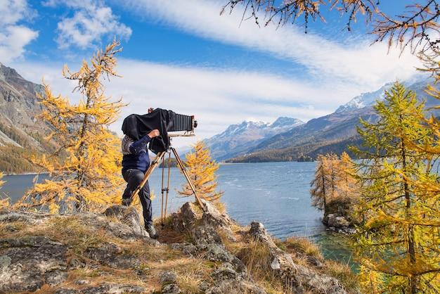 Fotografo di paesaggi sotto la tenda della fotocamera a lastra