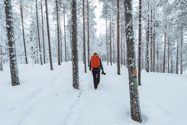 Fotografo paesaggista che fa trekking in una lapponia innevata, finlandia
