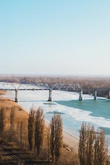 Paesaggio del ponte ferroviario su un fiume ghiacciato.
