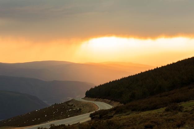 Strada del paesaggio tra montagne e valle verde al tramonto. foto di alta qualità