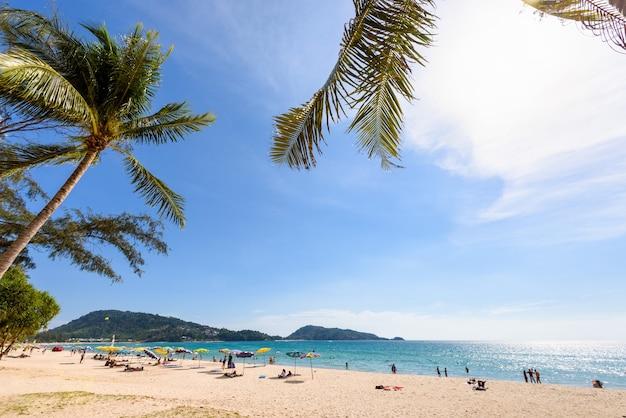 Paesaggio con palme o palme da cocco e turisti sulla spiaggia in riva al mare per lo sfondo, oceano delle andamane sotto il cielo del sole al tramonto viaggio estivo in asia, hat patong beach, isola di phuket, thailandia