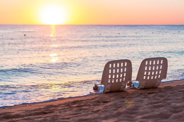 Paesaggio di due sedie a sdraio solitarie vicino al mare e alla bellissima alba