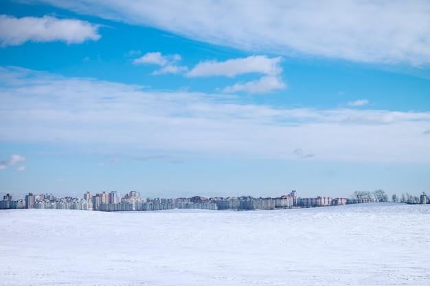 Paesaggio di grattacieli urbani, sulla superficie del cielo azzurro e della neve bianca