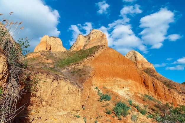 Scogliere del capo dell'argilla di vista del paesaggio. erba verde, prati coltivati sui pendii delle montagne argillose contro il cielo blu. colline di montagna e pendii del capo sono ricoperte di mezza erba e piante. muro di argilla.