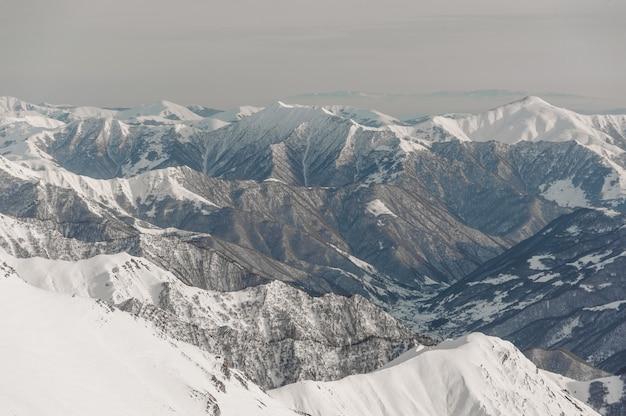 Paesaggio delle montagne di inverno coperte di neve sotto il cielo