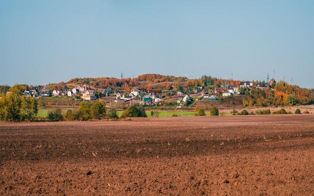 Paesaggio con terreno agricolo con un villaggio sullo sfondo