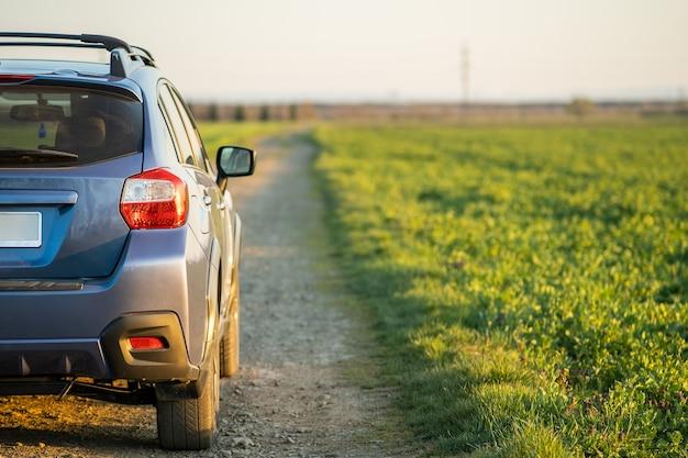 Paesaggio con fuoristrada blu su strada sterrata. viaggio in auto, avventura nella fauna selvatica, spedizione o viaggio estremo su un'automobile suv. veicolo fuoristrada 4x4 in campo all'alba.