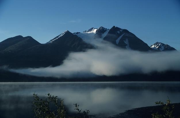 Paesaggio con montagne nebbiose contro il cielo blu