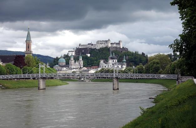 Paesaggio, con il castello di hohensalzburg sulla montagna festung a salisburgo, austria vista dal ponte sul fiume salzach in tempo nuvoloso