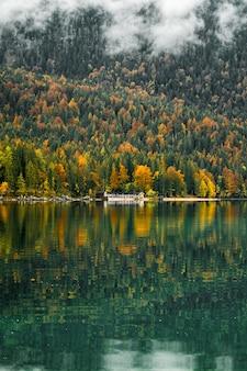 Paesaggio con lago, foresta, casa nelle montagne bavaresi, germania