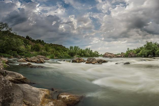 Paesaggio con maestoso cielo sopra il fiume di montagna