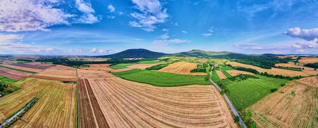 Paesaggio con montagne, campi verdi e villaggio di campagna, vista aerea