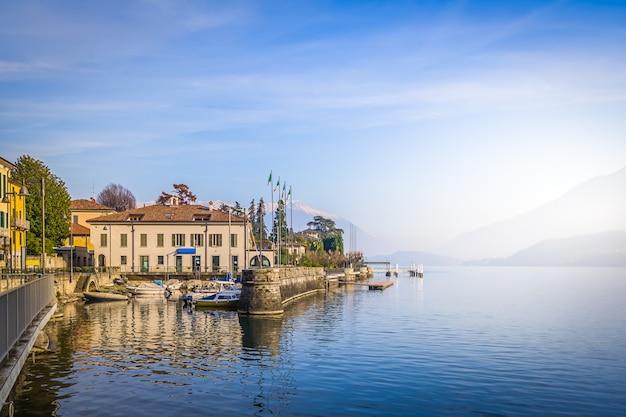 Paesaggio con cime innevate delle alpi e la calma superficie dell'acqua del lago di como