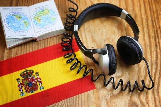Cuffie e bandiera del corso di lingua sul tavolo di legno