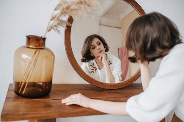 Languida donna in abito bianco davanti allo specchio. bella bruna con i capelli corti al chiuso. da dietro.