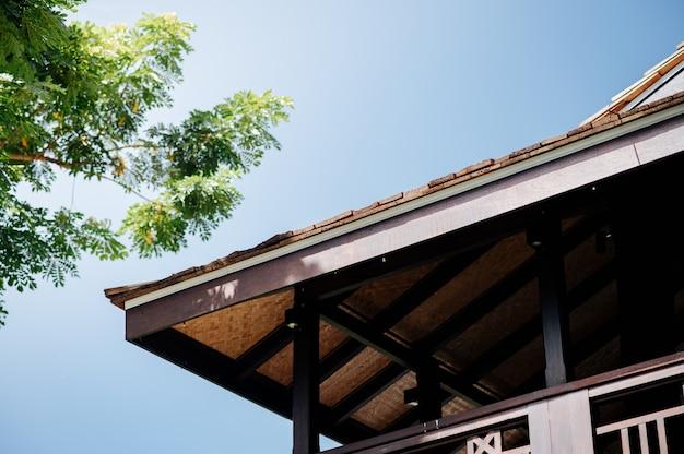 Casa in stile lanna con grandi alberi, cielo sereno