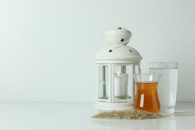 Lanterna, bicchieri di tè e acqua su bianco