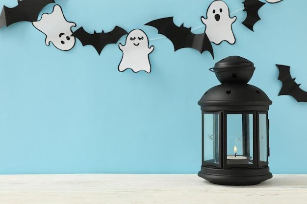 Lanterna, fantasmi di carta e pipistrelli su sfondo blu