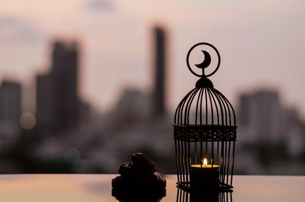 Lanterna e piccolo piatto di datteri frutta con sfondo di città per il ramadan kareem.