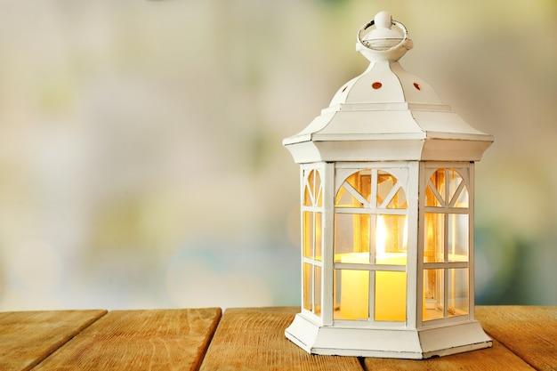 Lanterna su superficie di legno e sfondo sfocato