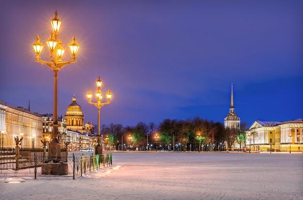 Lanterne sulla piazza del palazzo a san pietroburgo e la cattedrale di sant'isacco e l'ammiragliato lontano