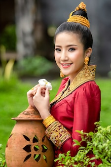 Volto di ragazza lao in abito tradizionale con fiore nazionale del laos, fiore champa.
