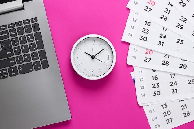 Laptop e sveglia, calendario mensile sulla superficie rosa. il tempo corre via. il concetto di scadenze urgenti sul lavoro e impegni