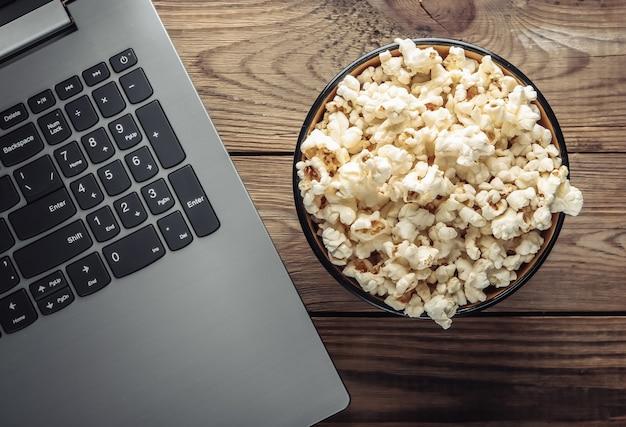Computer portatile, ciotola di popcorn sulla tavola di legno