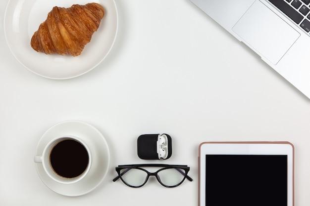 Laptop, caffè, tablet, croissant, occhiali, cuffie nel caso su sfondo bianco