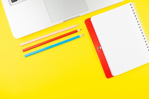 Computer portatile, pensils colorati e pianificatore di blocco note su sfondo giallo. disteso. copia spazio.