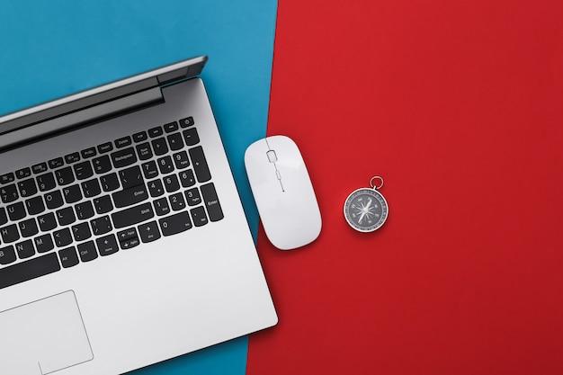 Computer portatile e bussola su rosso-blu. concetto di viaggio o business online