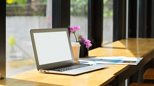 Modello dello schermo in bianco del computer portatile sulla tavola di legno in caffetteria con luce solare naturale attraverso la finestra