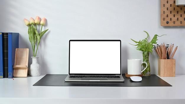 Computer portatile, tazza di caffè, libri, pianta d'appartamento e portamatite in ufficio a casa.