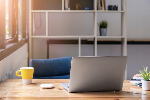Mockup di computer portatile sulla tavola di legno con la luce del mattino.
