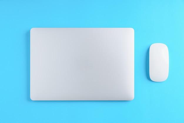 Computer portatile e mouse su sfondo blu sopra vista