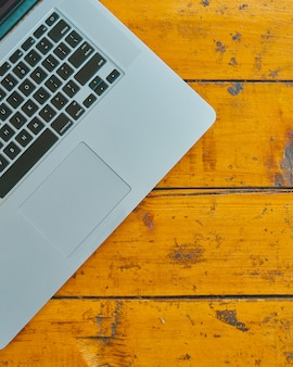 Computer portatile sul fondo della tavola dell'ufficio. vista dall'alto del minicomputer su tavola di legno.