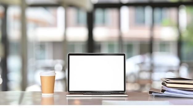 Computer portatile, bicchiere di carta e libri sulla scrivania bianca.