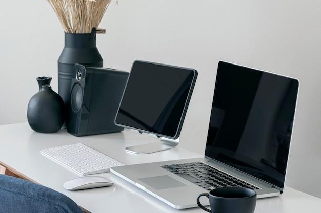Computer portatile e tablet con schermo nero su tavolo bianco, area di lavoro creativa mockup con dispositivo portatile.